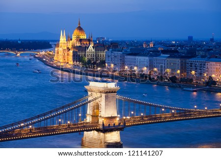 Budapest cityscape at night with Chain Bridge over Danube river and Parliament Building in the background.