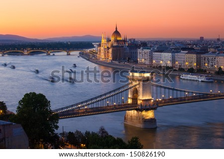 Budapest cityscape sunset with Chain Bridge in front over Danube river and Parliament Building in the background.