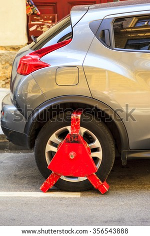 BUDAPEST HUNGARY - APRIL 29 2014: Wheel lock on an illegally parked car in downtown Budapest, there are limited spots. Although there are few incident in large in Budapest. - stock photo