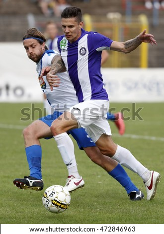 BUDAPEST, HUNGARY - AUGUST 21, 2016: Benjamin Balazs (R) of Ujpest FC duels for the ball with Adam Vass (L) of MTK during the OTP Bank Liga match between Ujpest FC and MTK at Illovszky Stadium.