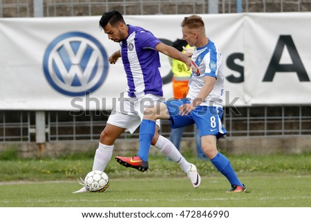BUDAPEST, HUNGARY - AUGUST 21, 2016: Nemanja Andric (L) of Ujpest tries to cross the ball next to Balint Vogyicska #8 of MTK during the OTP Bank Liga match between Ujpest and MTK at Illovszky Stadium.