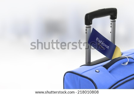 Budapest, Hungary. Blue suitcase with label at airport. - stock photo