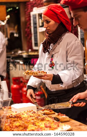 BUDAPEST, HUNGARY - DEC 03: Unidentified woman serves food in the Budapest Christmas Fair on Dec. 03, 2012 in Budapest. Budapest Christmas Fair is one of the most popular Christmas markets in Europe. - stock photo