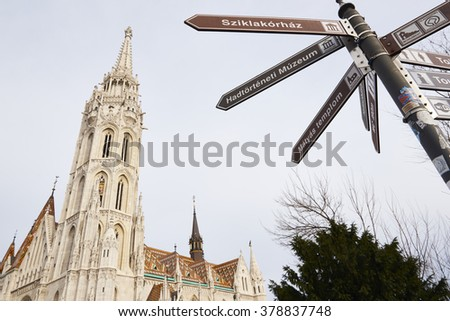 BUDAPEST, HUNGARY - FEBRUARY 02:Low angle shot of directional sign with Saint Matthias Church tower in the background. February 02, 2016 in Budapest. - stock photo