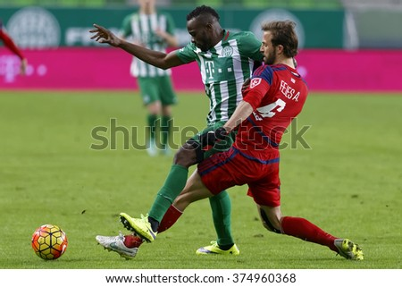 BUDAPEST, HUNGARY - FEBRUARY 10, 2016: Roland Lamah of Ferencvaros (l) is tackled by Andras Fejes of Videoton during Ferencvaros - Videoton Hungarian Cup quarter final football match at Groupama Arena - stock photo