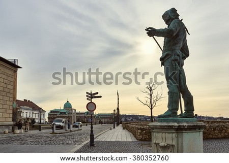 BUDAPEST, HUNGARY - FEBRUARY 02: Statue of a Hussar inspecting the edge of his sword, with Buda Castle in the background. February 02, 2016 in Budapest. - stock photo