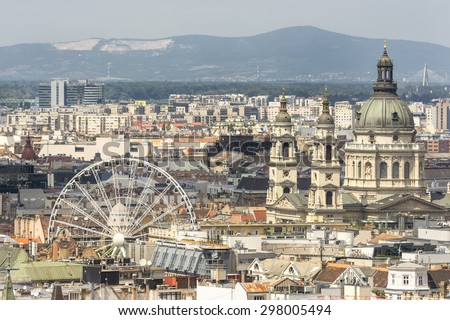 BUDAPEST, HUNGARY, JULY 10, 2015: Aerial view of Sziget's Eye (ferris wheel) and St. Stephen's Basilica with many rooftops. - stock photo