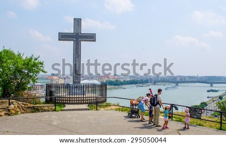 BUDAPEST, HUNGARY, JULY 29, 2014: family is admiring danube river from place with cross on gellert hegy hill. szabadsag bridge is behind.