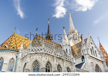 BUDAPEST, HUNGARY, JULY 10,2015: Matthias Church exterior, a Roman Catholic church located in Budapest, Hungary, in front of the Fisherman's Bastion at the heart of Buda's Castle District. - stock photo
