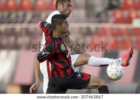 BUDAPEST, HUNGARY - JULY 27, 2014: Next to Marku Kristi of Honved (r), Burak Yilmaz of Galata shoots on goal during Budapest Honved vs. Galatasaray football match at Bozsik Stadium.
