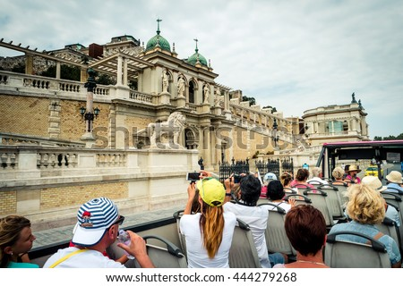 Budapest, Hungary - July 07, 2015: tourists on bus taking pictures near lower part of Buda castle - stock photo