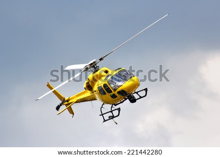 BUDAPEST, HUNGARY - JULY 26, 2014: Yellow helicopter Eurocopter AS-355N Ecureuil 2 at the sky above the Hungaroring Formula One Race Track. - stock photo