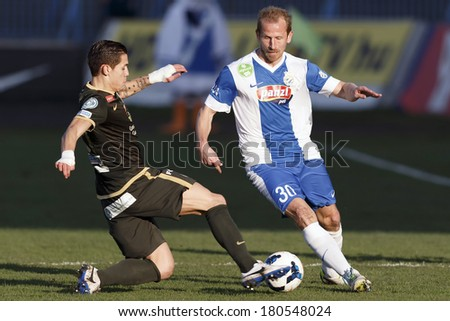 BUDAPEST, HUNGARY - MARCH 8, 2014:  Muhamed Besic of Ferencvaros tries to tackle Sandor Torghelle of MTK (r) during MTK Budapest vs. Ferencvaros OTP Bank League football match at Hidegkuti Stadium