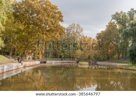 BUDAPEST, HUNGARY - OCTOBER 26, 2015: Heroes Square Parl with lake and autumn trees. Local People and seagull in background
