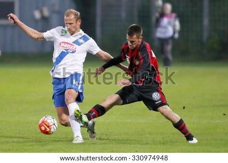 BUDAPEST, HUNGARY - OCTOBER 24, 2015: Sandor Torghelle of MTK (l) is tackled by Filip Holender of Honved during MTK vs. Honved OTP Bank League football match in Illovszky Stadium. - stock photo