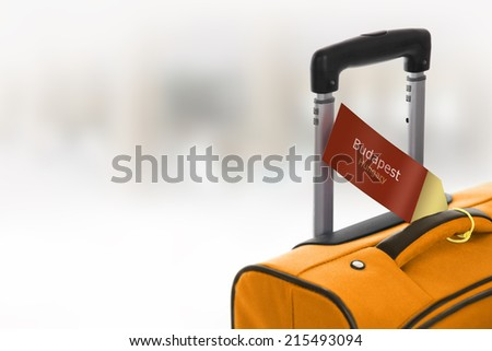 Budapest, Hungary. Orange suitcase with label at airport. - stock photo