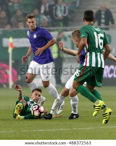 BUDAPEST, HUNGARY - SEPTEMBER 24, 2016: Dominik Nagy (L1) of Ferencvaros lies on the ground before Jozsef Windecker (L2) of Ujpest FC during Ferencvaros v Ujpest OTP Bank Liga match at Groupama Arena