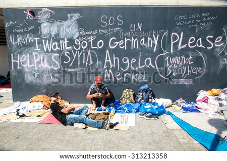 BUDAPEST, HUNGARY - SEPTEMBER 04: Syrian refugees demand help from Germany written on a wall at the Train Station Keleti Palyudvar on September 04, 2015 in Budapest, Hungary.   - stock photo