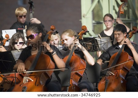 BUDAPEST - JULY 22: Members of Texas Youth Orchestra perform on stage at Millenaris July 22, 2009 in Budapest, Hungary. - stock photo