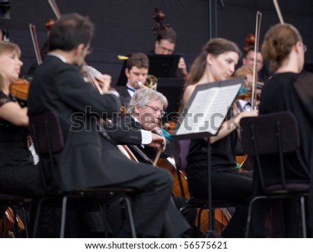 BUDAPEST - JUNE 27: Members of the Budapesti Fesztivalzenekar Phillharmonic  Orchestra perform on stage at Hosok Tere  on June 27, 2010 in Budapest, Hungary. - stock photo
