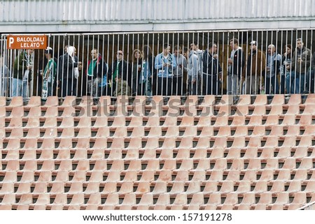 BUDAPEST - OCTOBER 6: Fans of FTC watch the game behind the separator grid of the closed stand during FTC vs. Honved OTP Bank League match at Puskas Stadium on October 6, 2013 in Budapest, Hungary.  - stock photo
