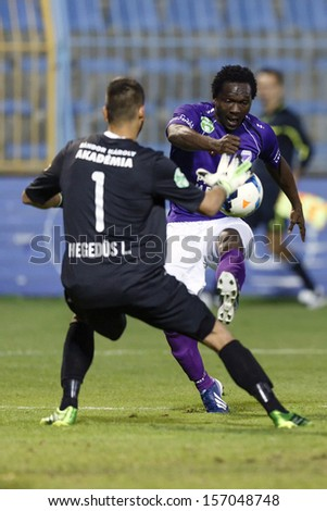 BUDAPEST - OCTOBER 5: Lajos Hegedus of MTK (L) saves the shot of Ousmane Barry of KTE during MTK vs. KTE OTP Bank League match at Hidegkuti Stadium on October 5, 2013 in Budapest, Hungary.  - stock photo