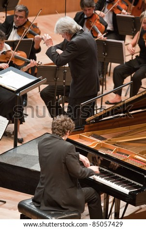 "BUDAPEST - SEPT 18: Magyar Radio Symphonic Orchestra perform on concert at ""Palace of Art"" Budapest Sept 18, 2011 in Budapest, Hungary. Conductor: Gergely Vajda, pianist: Namoradze Nicolas - stock photo"