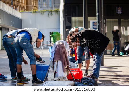 BUDAPEST - SEPTEMBER 7: war refugees bathing and drinking at Keleti Railway Station on 7 September 2015 in Budapest, Hungary. Refugees are arriving constantly to Hungary on the way to Germany. - stock photo