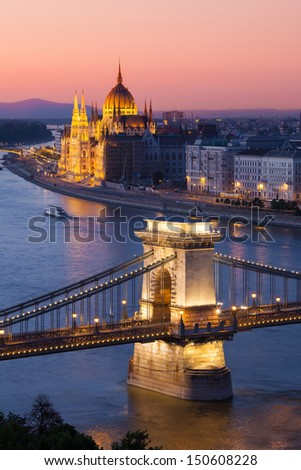 Budapest sunset cityscape with Chain Bridge in front over Danube river and Parliament Building in the background.