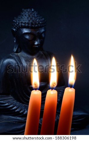 buddha behind candles (cool lighting) - stock photo