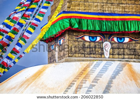 Buddha eyes close up with prayer flags at Bodhnath stupa in Kathmandu valley, Nepal - stock photo