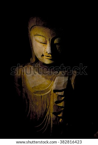 Buddha face in Light, wood carving of a sculpture of Buddha with focus on the downcast eye, very shallow depth of field.