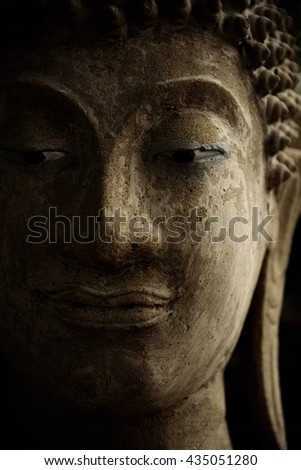 Buddha face with light and shadow. - stock photo