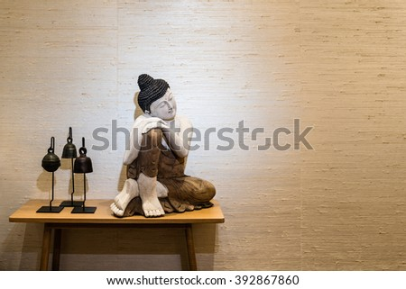 Buddha figurine on a side table with decorative parquet floor