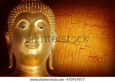 Buddha gold statue close-up on wooden background