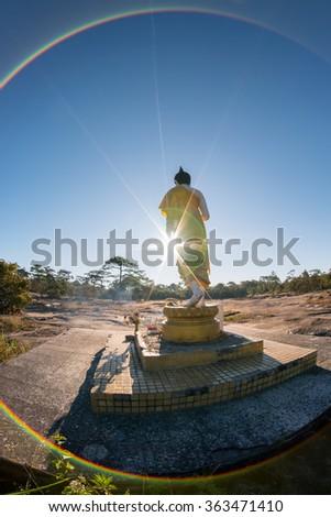 Buddha image with sunrise and flare, Phu Kradueng, Loei, Thailand - stock photo