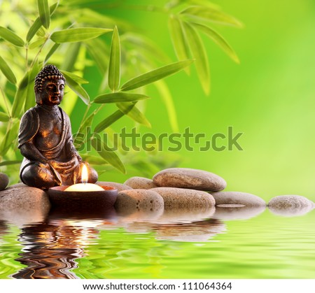 Buddha in meditation with burning candle,bamboo leaf and zen stones. - stock photo