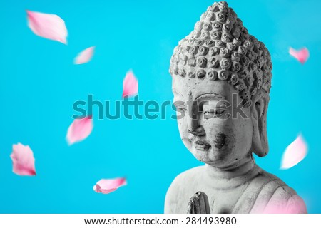 Buddha in meditation with flower petals - stock photo