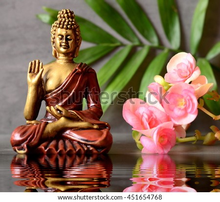 Buddha is sitting in ZEN garden with  flower, palm and balance stones - stock photo
