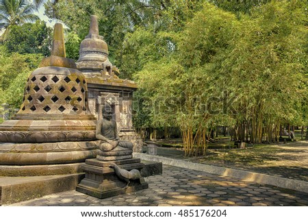 Buddha meditating in front of stone stupas in Mendut temple, Indonesia