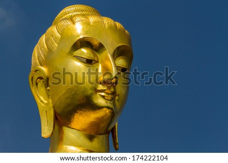 Buddha portrait isolated on blue sky in thailand.