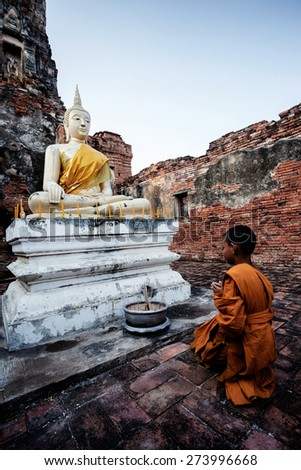 Buddha statue and Novice at Ayutthaya historical park in Thailand - stock photo