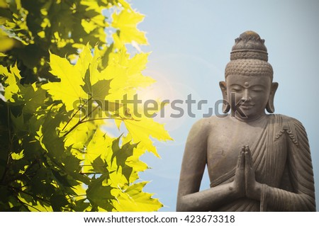 Buddha statue and yellow maple - asian culture - stock photo