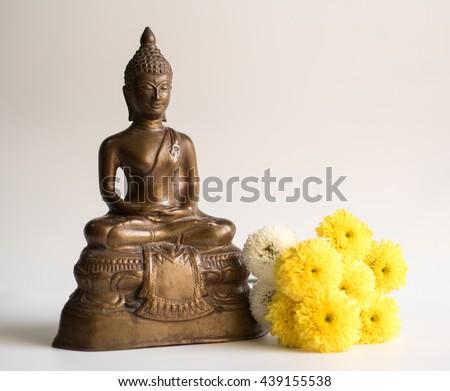 Buddha Statue beside Chrysanthemum Flower in warm and cozy tone - stock photo