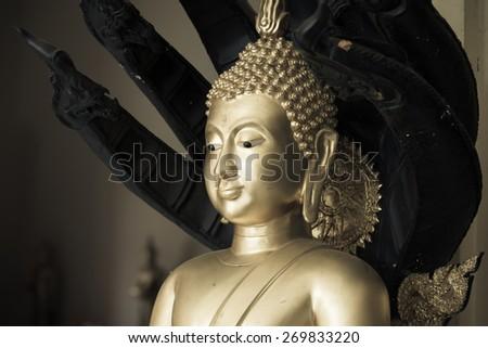 Buddha statue closeup in golden vintage tone - stock photo