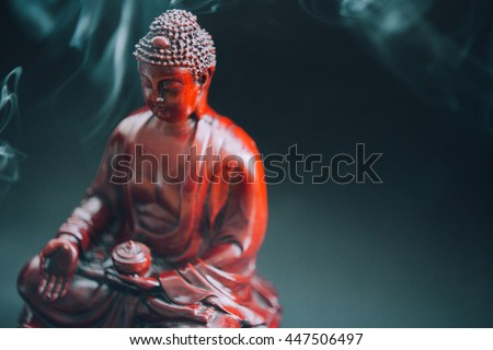 Buddha statue decorated with offerings and flowers. Murti Buddha in the smoke from the incense and floral decorations. Buddhism and its deities, Gautama Buddha FILM TEXTURE
