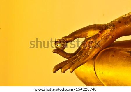 buddha statue hands on yellow background - stock photo