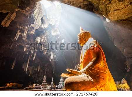 Buddha Statue in cave light ray