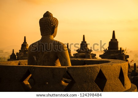 Buddha statue in open stupa in Borobudur, or Barabudur, temple Jogjakarta, Java, Indonesia at sunrise. It is a 9th-century Mahayana temple and the biggest  Buddhist Temple in Indonesia. - stock photo