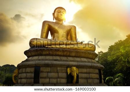 Buddha statue over scenic sunset sky in Colombo, Sri Lanka - stock photo